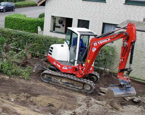excavator grading and compacting soil