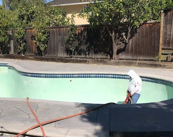 swimming pool demolition in Santa Cruz begins with jack hammering the plaster walls