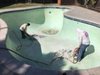 using a jackhammer on a swimming pool removal